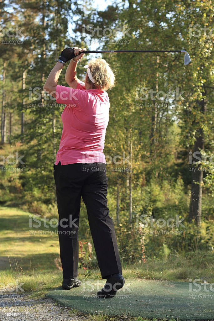Woman hit the ball in a golf swing stock photo