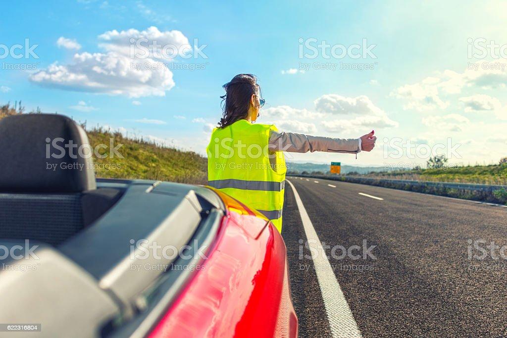 Woman hitchhiking at broken car stock photo