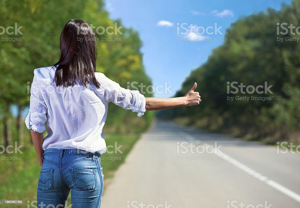 Woman hitchhiking back view stock photo