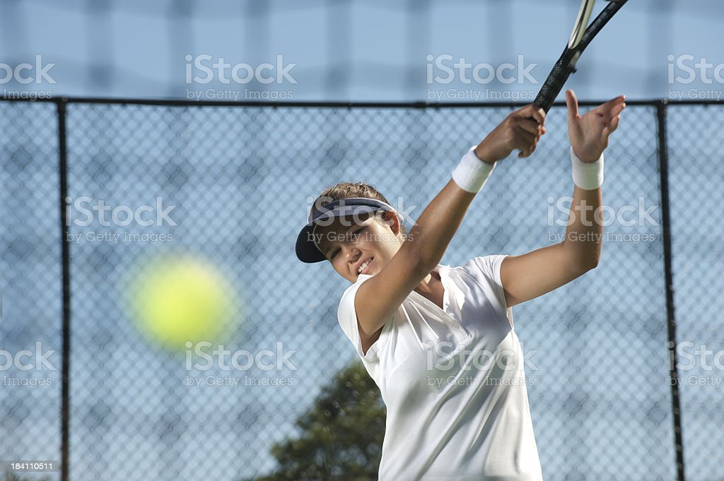 Woman hitting an tennis ball royalty-free stock photo