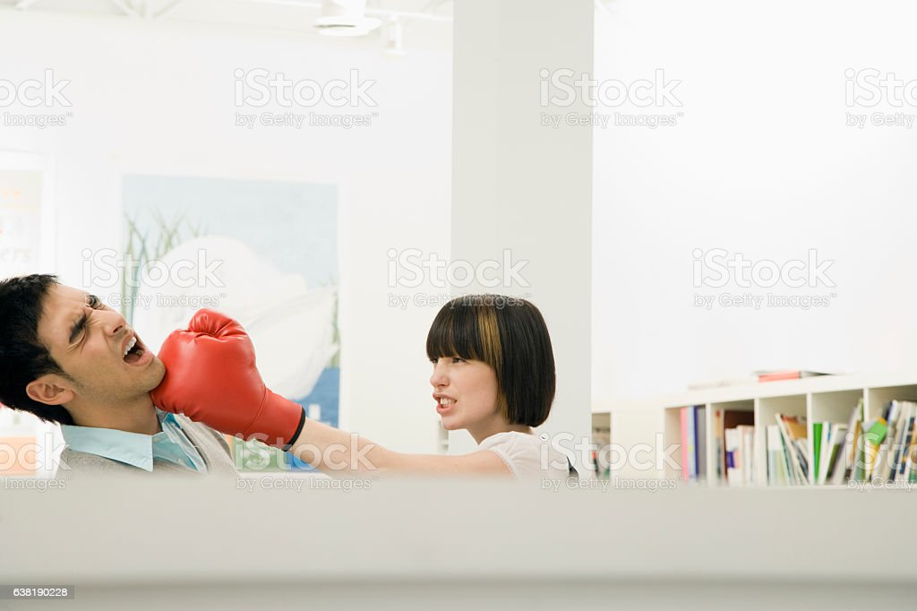 Woman hitting man with boxing glove in office cubicle fight stock photo