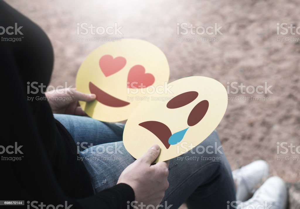 Woman holding 2 cardboard emoticons in hand. Love heart and crying smiley faces. Heartbroken or confused girl having   mixed feelings about emotions. Two modern opposite expression icons printed on paper. stock photo
