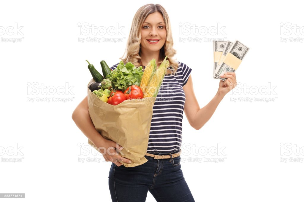 Woman holding a bag of groceries and stacks of money stock photo
