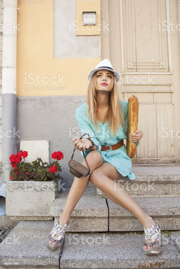 A woman holding a baguette while sitting on outdoor stairs stock photo