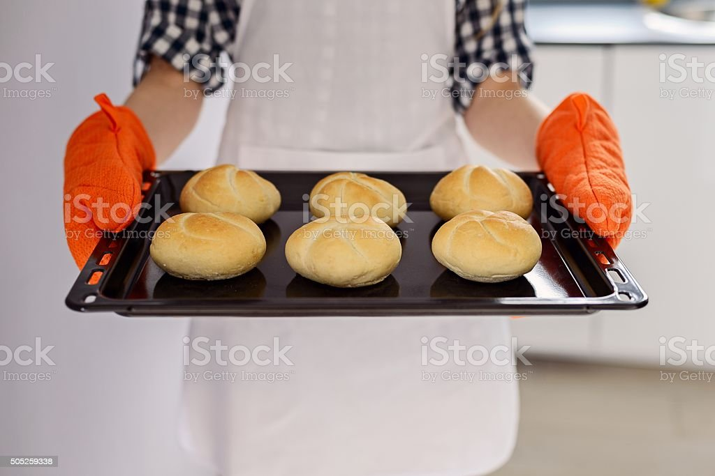 woman holding a baking tray with freshly baked bread rolls. stock photo