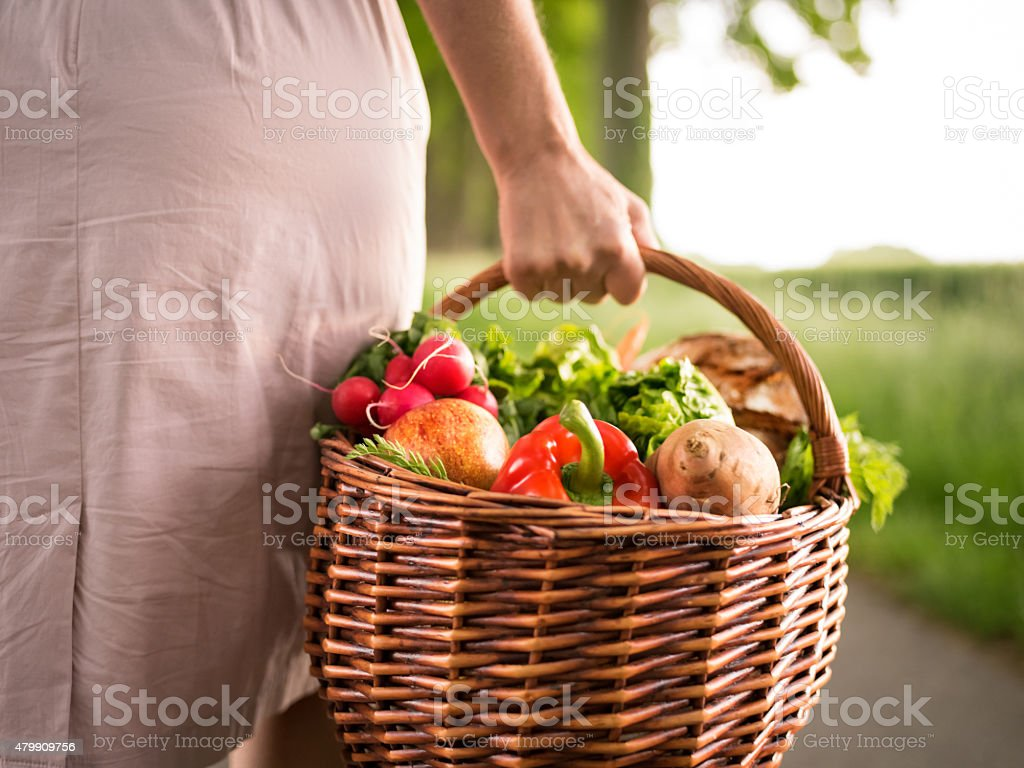Woman holding a basket of vegetables in a park stock photo