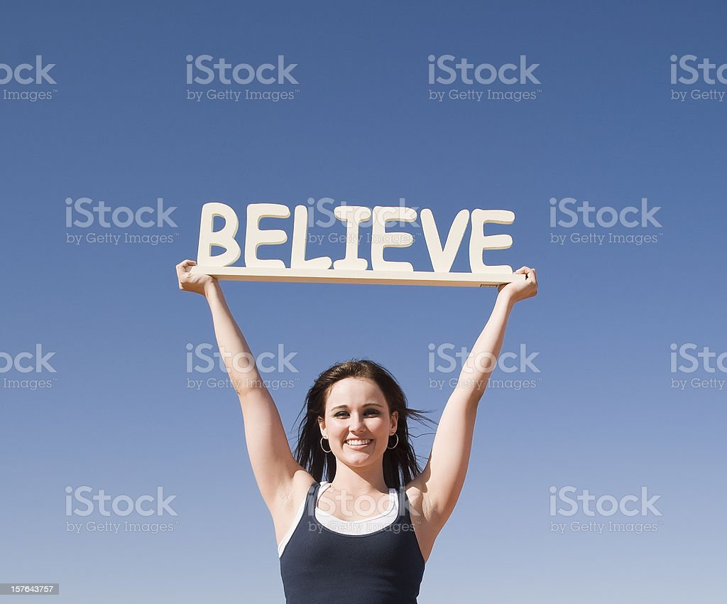 Woman Holding a Believe Sign royalty-free stock photo