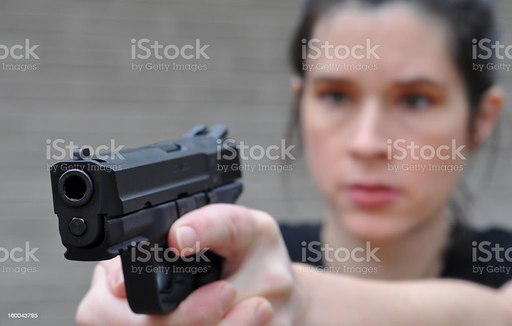 Woman holding a black revolver with the focus on the gun stock photo