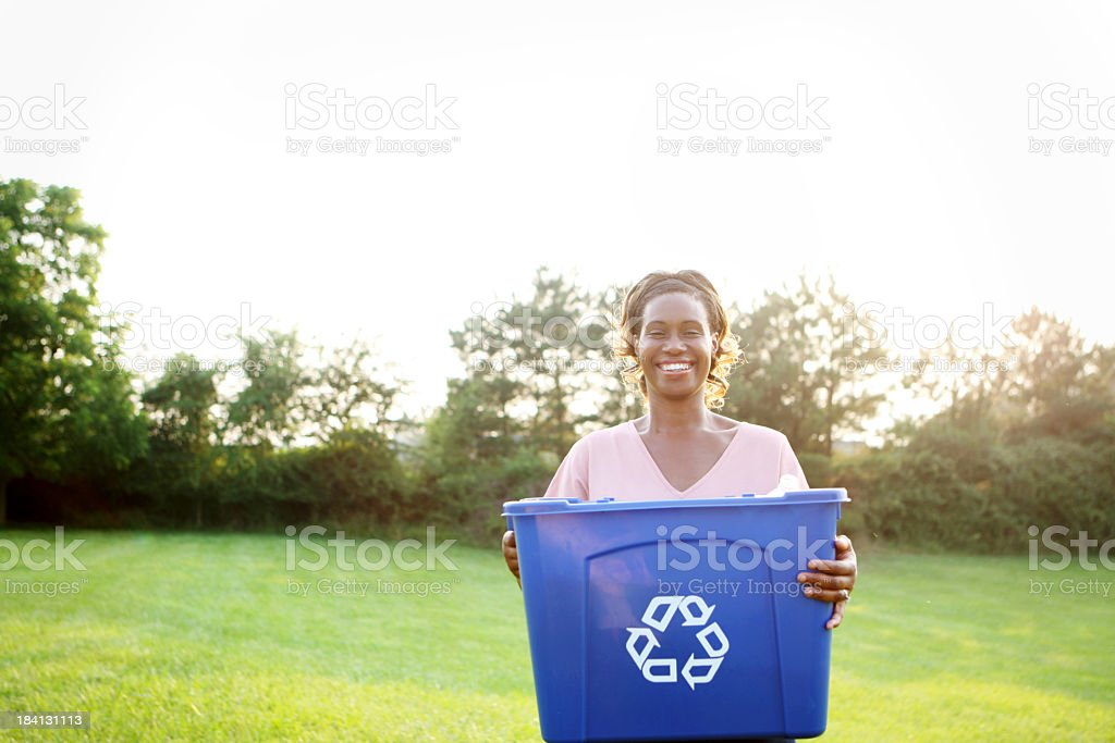 A woman holding a blue recycling bin outside stock photo