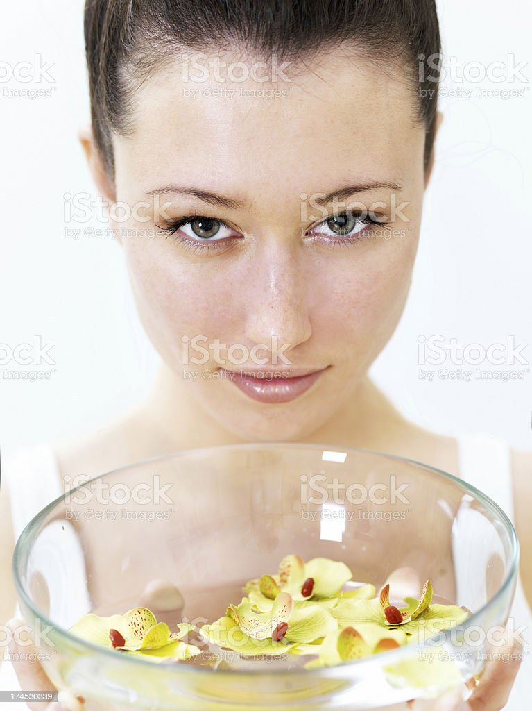 Woman holding a bowl of water with orchides royalty-free stock photo