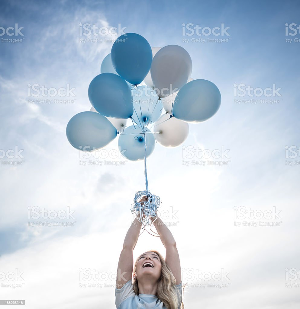 Woman holding a bunch of helium balloons outdoors stock photo