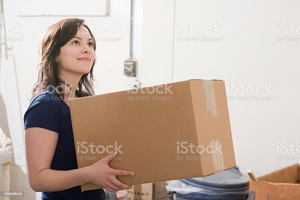 Woman holding a cardboard box stock photo
