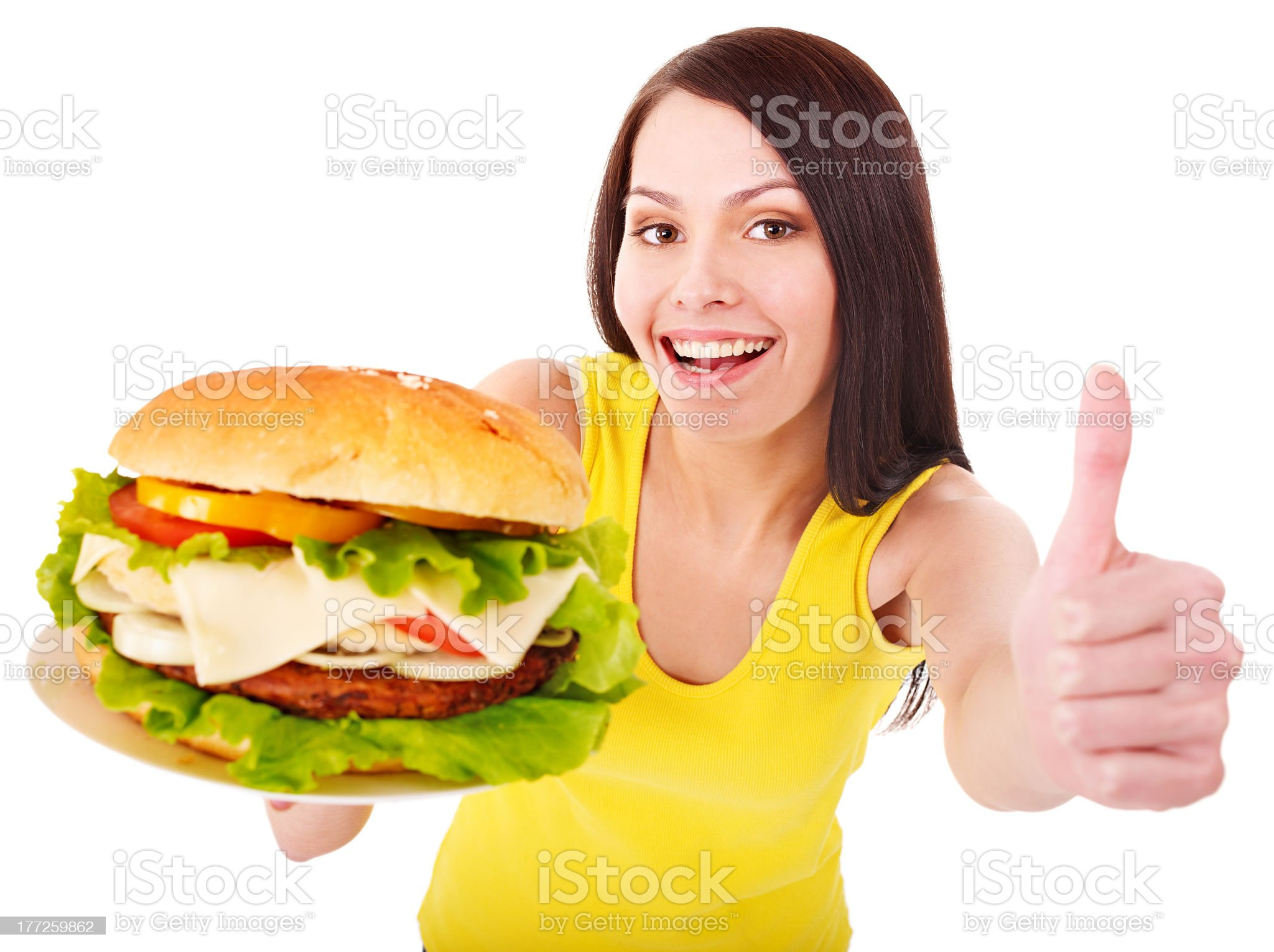Woman holding a cheeseburger with veggies giving thumbs up royalty-free stock photo