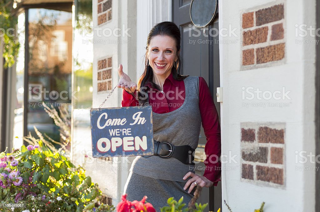A woman holding a Come in we're open sign outside a store stock photo