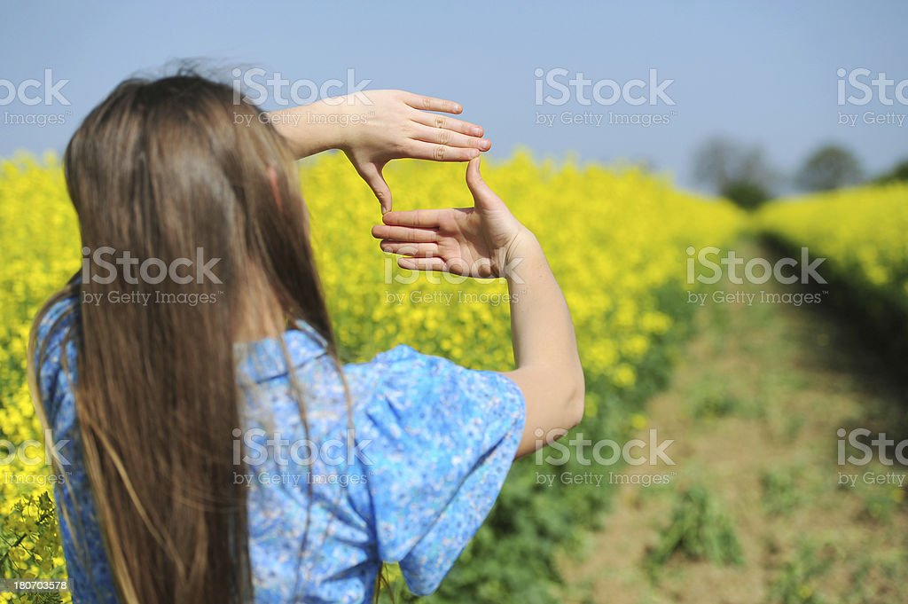 Woman holding a composition frame in nature. royalty-free stock photo