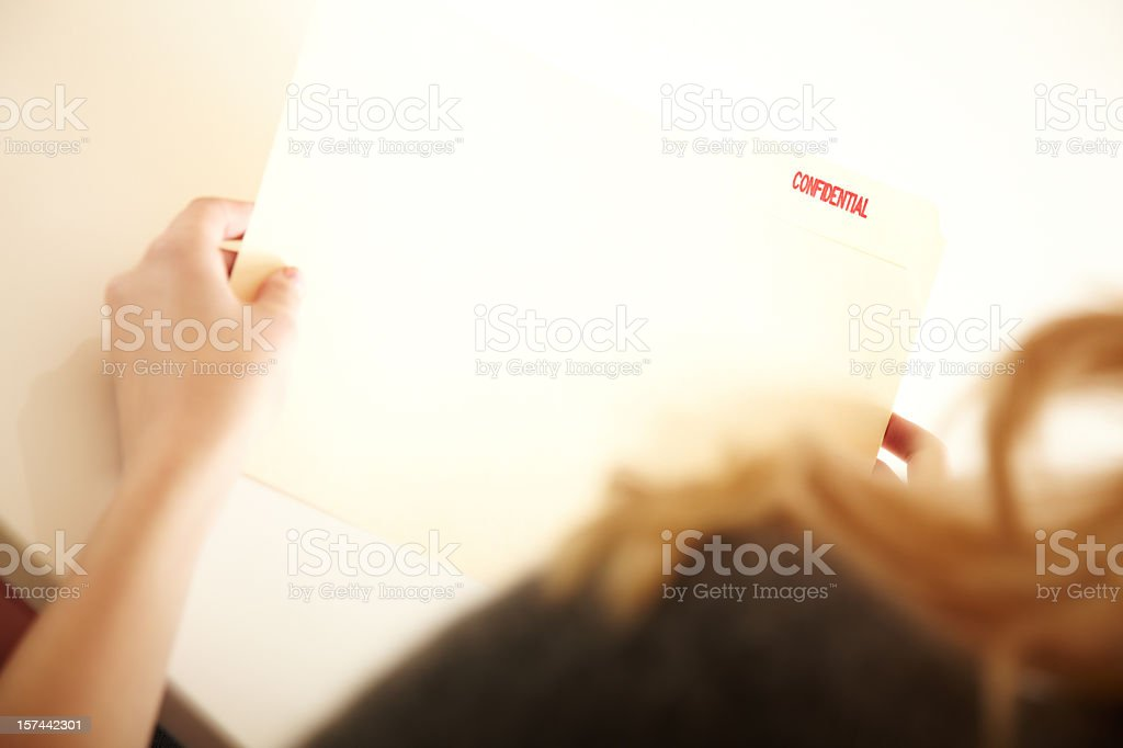 Woman Holding a Confidential folder of documents royalty-free stock photo