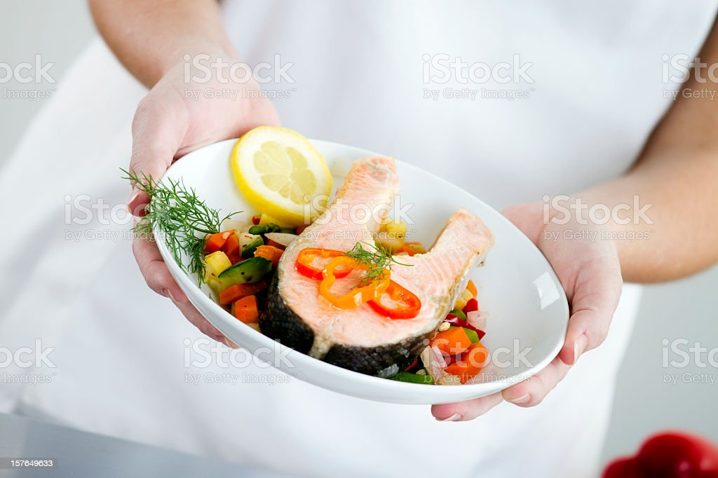 Woman holding a cooked salmon dish with vegetables garnish stock photo