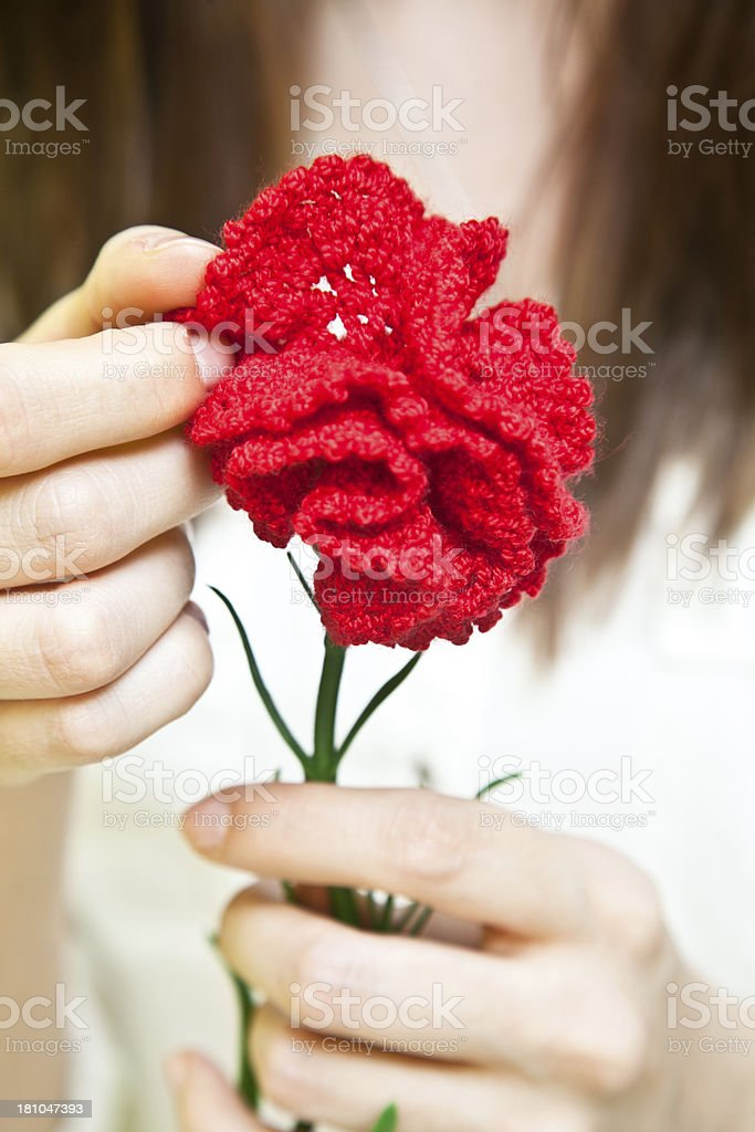 Woman holding a crochet-made red rose royalty-free stock photo