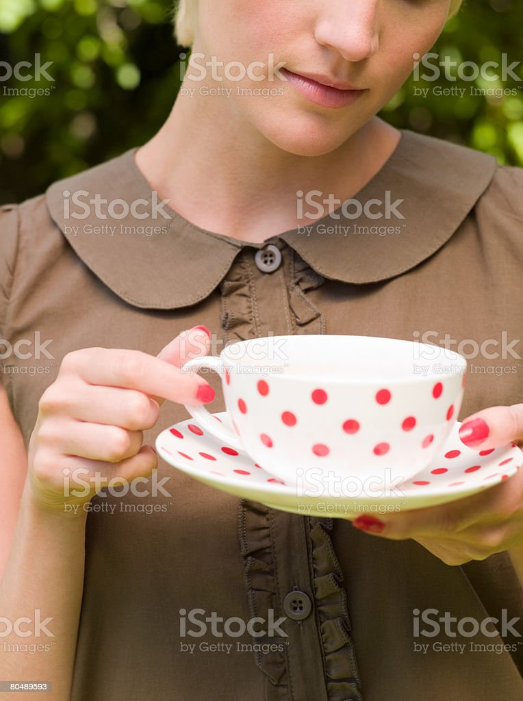 A woman holding a cup and saucer royalty-free stock photo