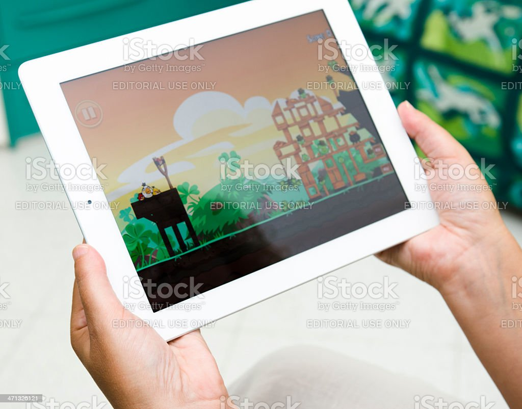 Woman holding a digital tablet and playing Angry Birds. royalty-free stock photo