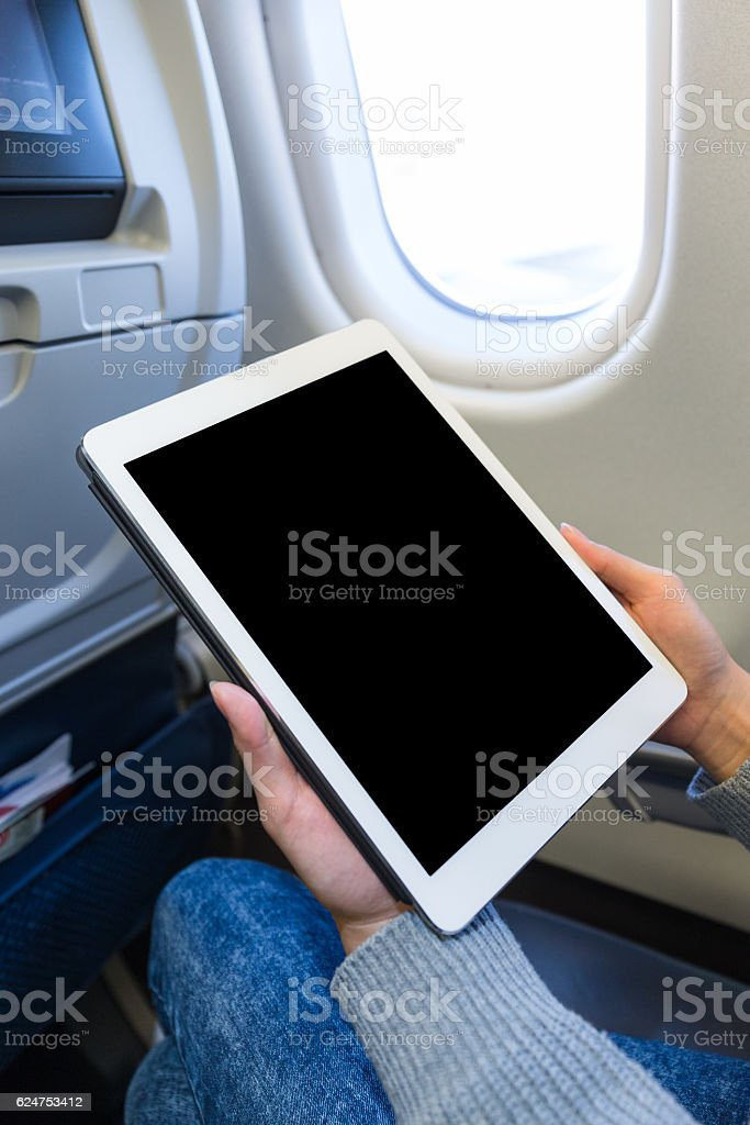 Woman holding a digital tablet on airplane stock photo