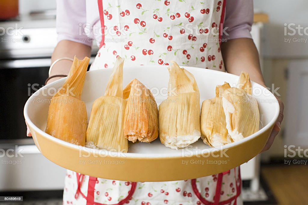 A woman holding a dish of tamales stock photo