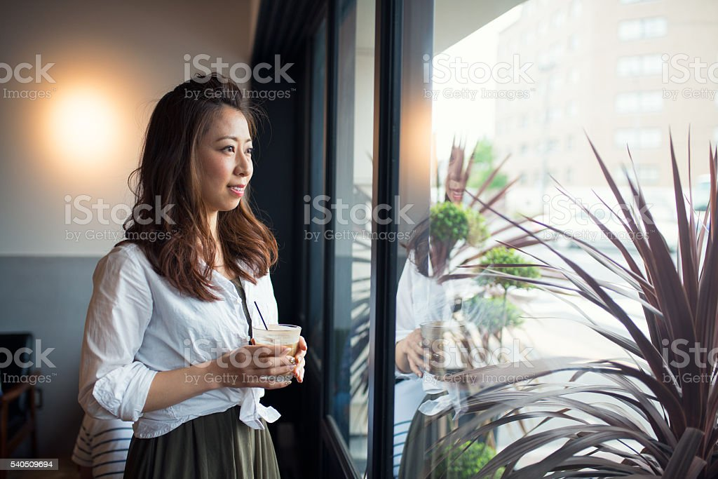 Woman holding a drink looking through window stock photo