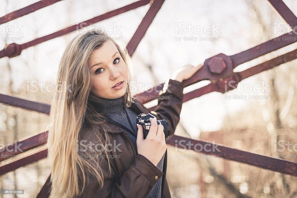 Woman Holding a Film Camera on an Old Truss Bridge stock photo