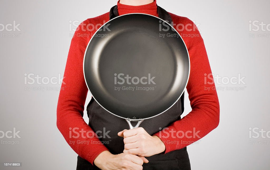 Woman holding a frying pan and not showing her face stock photo