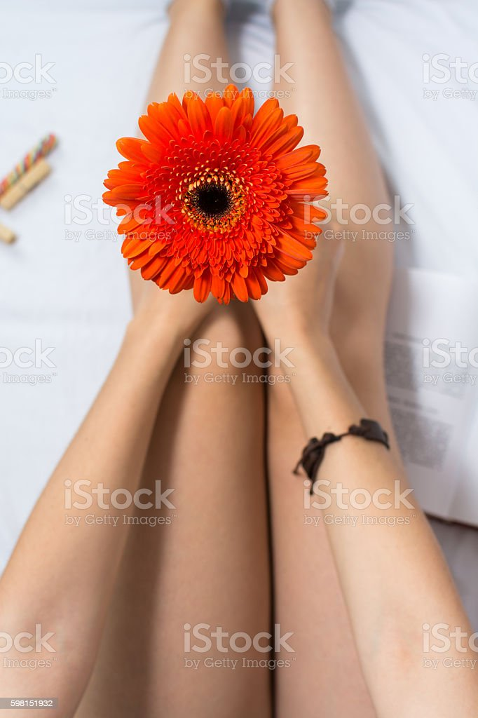 Woman holding a gerbera flower in bed stock photo