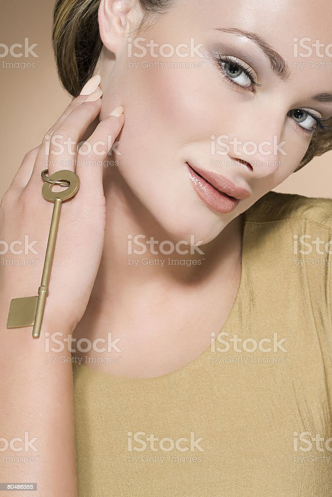 Woman holding a gold key royalty-free stock photo