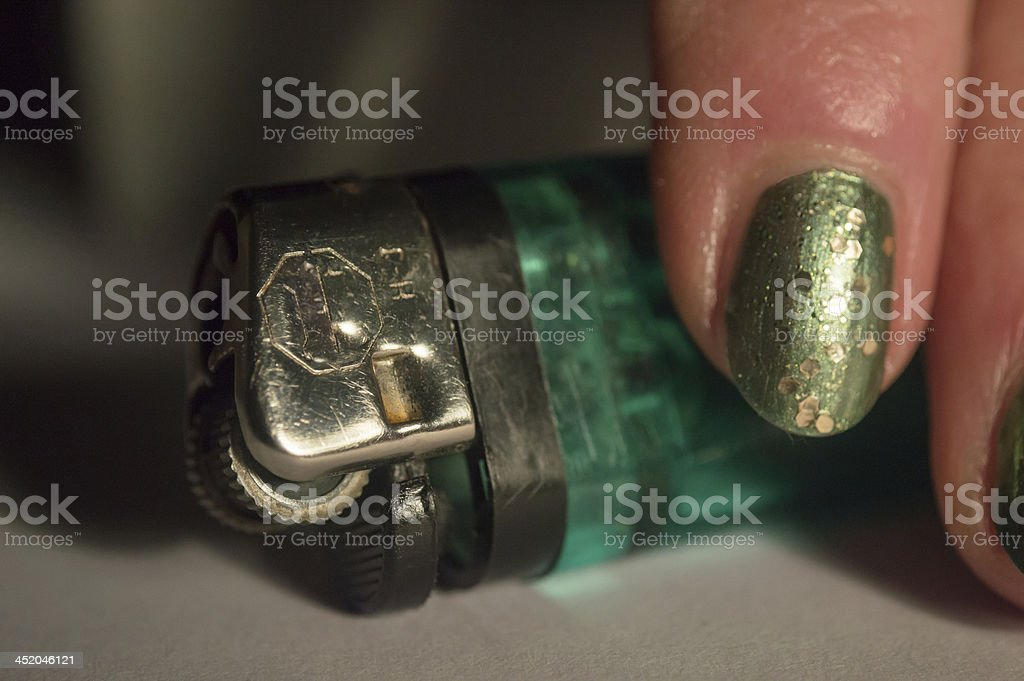 Woman Holding a Green Cigarette Lighter royalty-free stock photo