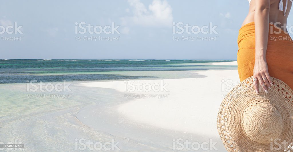 woman holding a hat at the beach in Anegada, BVI royalty-free stock photo