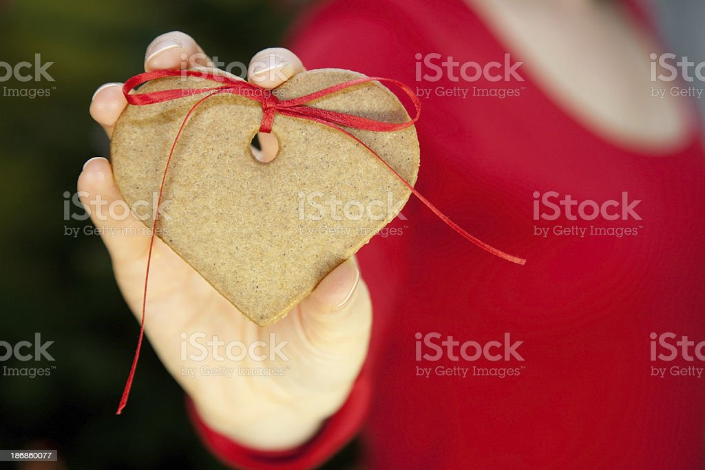 Woman holding a heart shaped cookie royalty-free stock photo