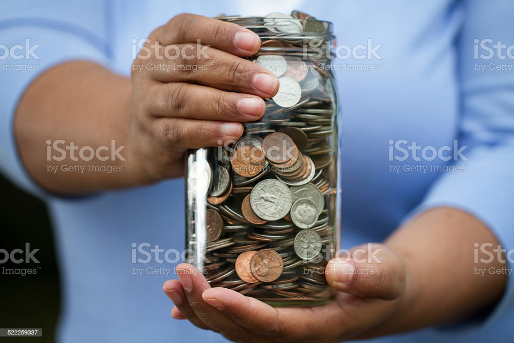 Woman holding a jar of money stock photo