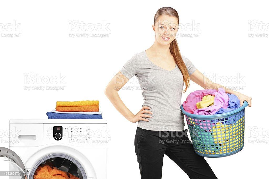 Woman holding a laundry basket next to washing machine stock photo