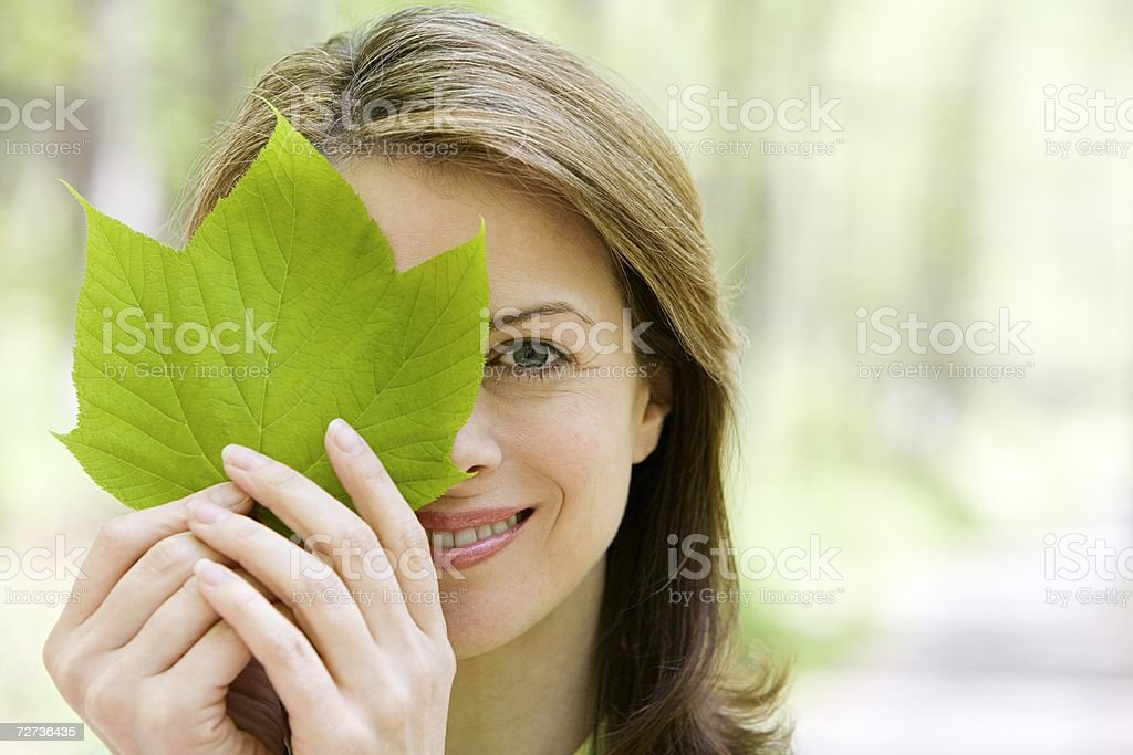Woman holding a leaf to her eye stock photo