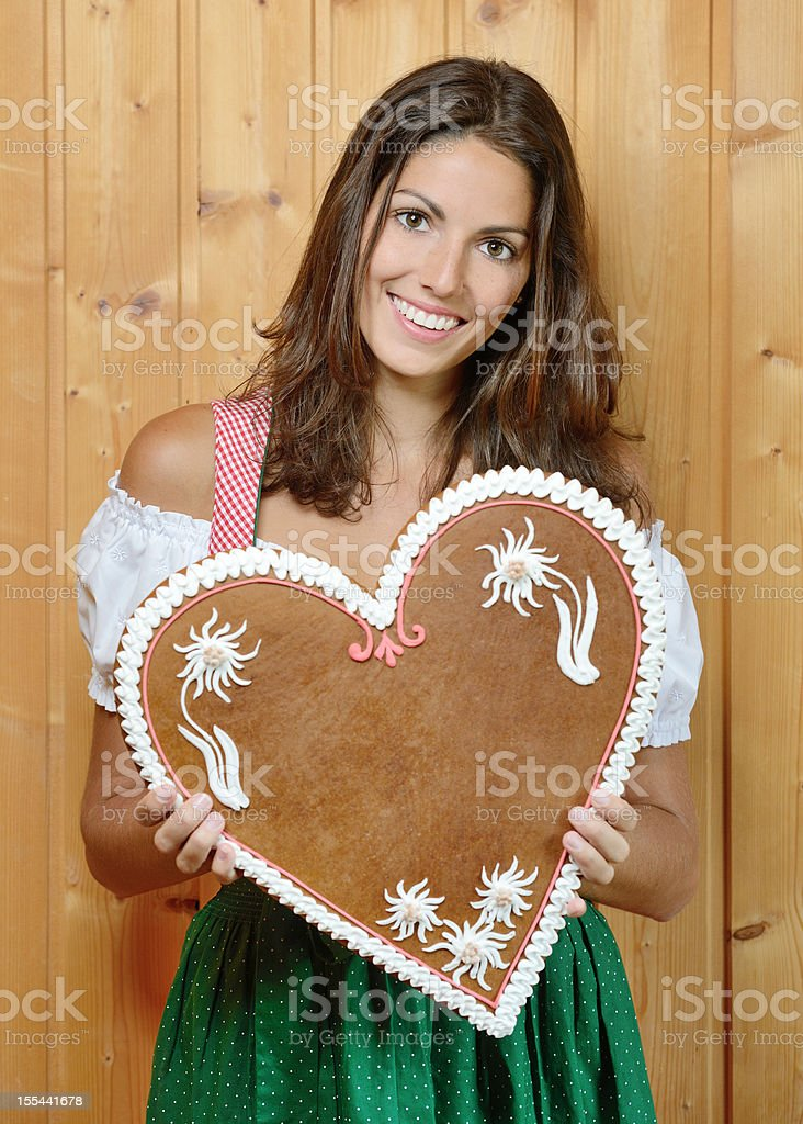 Woman holding a Lebkuchen Gingerbread Heart with Copy Space (XXXL) royalty-free stock photo
