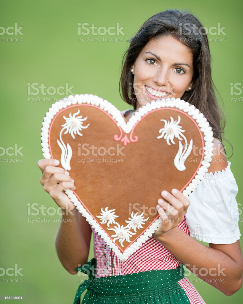 Woman holding a Lebkuchen Gingerbread Heart with Copy Space (XXXL) stock photo