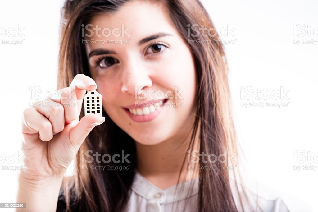 woman holding a little house in her hand smiling stock photo