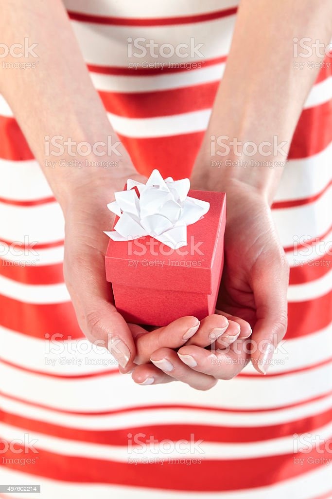 Woman holding a little red gift box stock photo