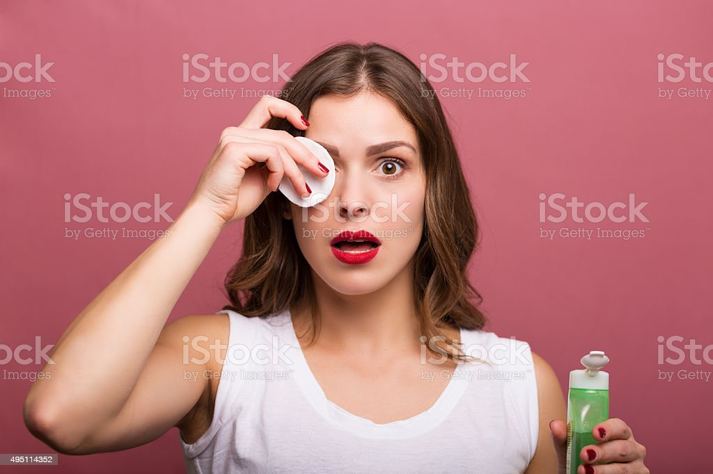 Woman holding a lotion and a cotton pad stock photo