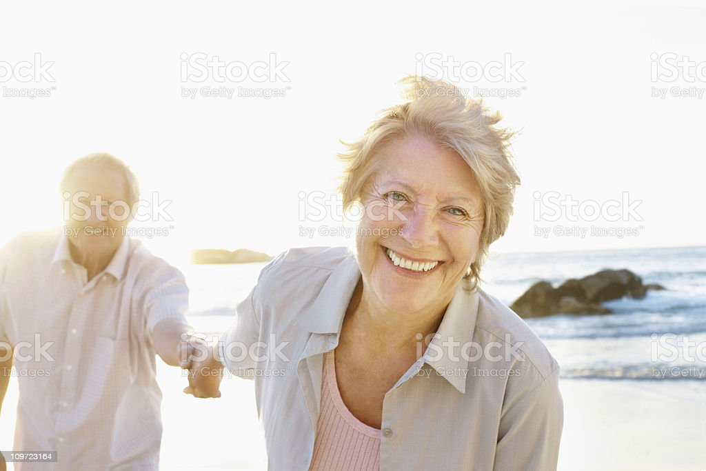 Woman holding a man's hand at the sea shore royalty-free stock photo