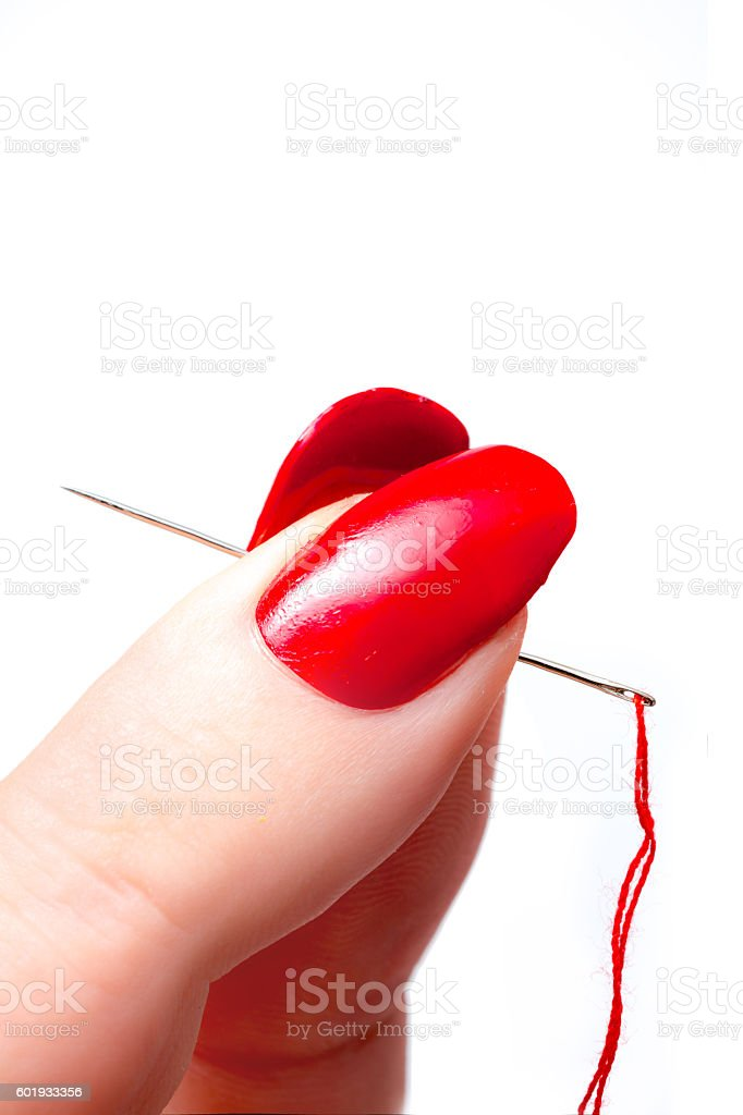 Woman holding a needle with red thread of yarn stock photo
