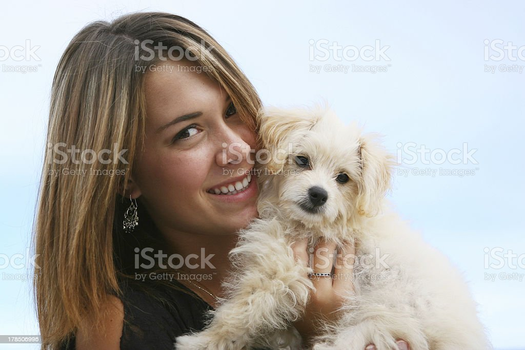 A woman holding a new puppy in her arms royalty-free stock photo