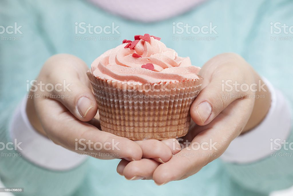 Woman holding a pink cupcake on white royalty-free stock photo