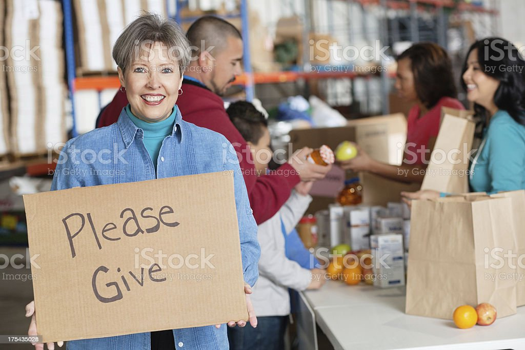 Woman holding a please give sign at donation center royalty-free stock photo