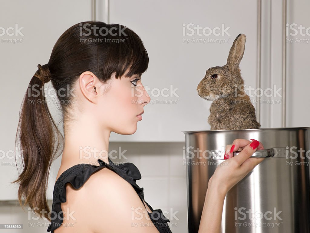 Woman holding a rabbit in a saucepan royalty-free stock photo