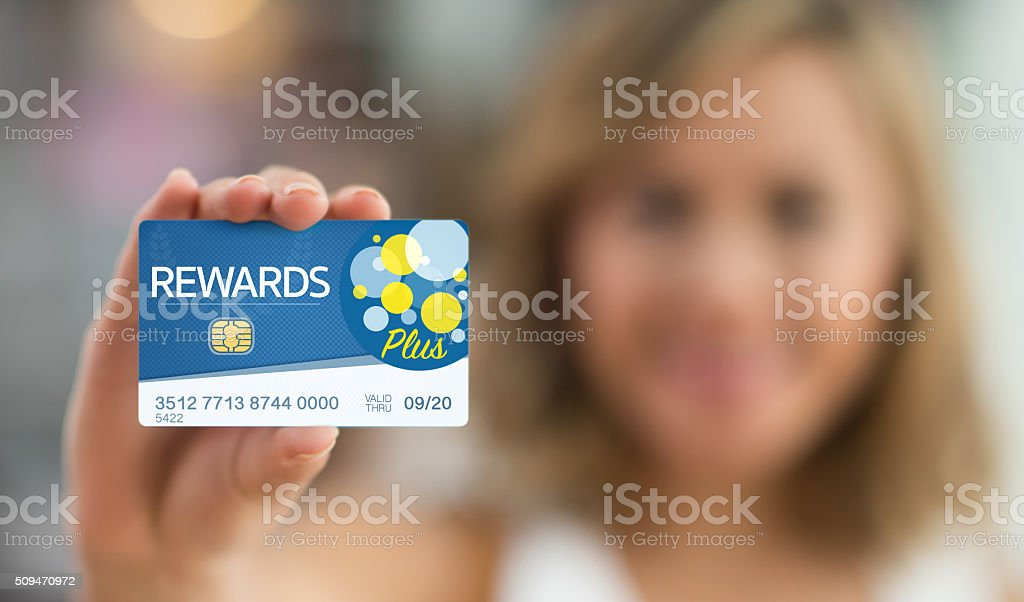 Woman holding a rewards card stock photo