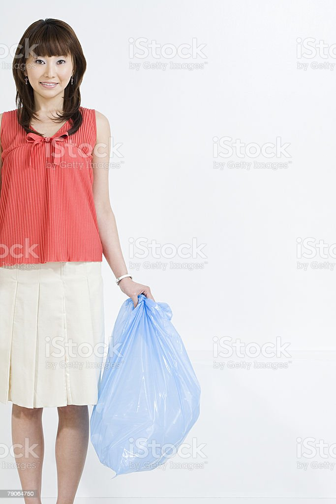 A woman holding a rubbish bag stock photo